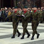 Poczet flagowy – trzech maszerujących żołnierzy 1 Brzeskiego Pułku Saperów maszerujących wraz ze złożoną flagą RP w kierunku masztu.