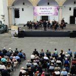 Orkiestra - artyści z instrumentami smyczkowymi oraz publiczność zgromadzona na dziedzińcu Zamku Piastów Śląskich