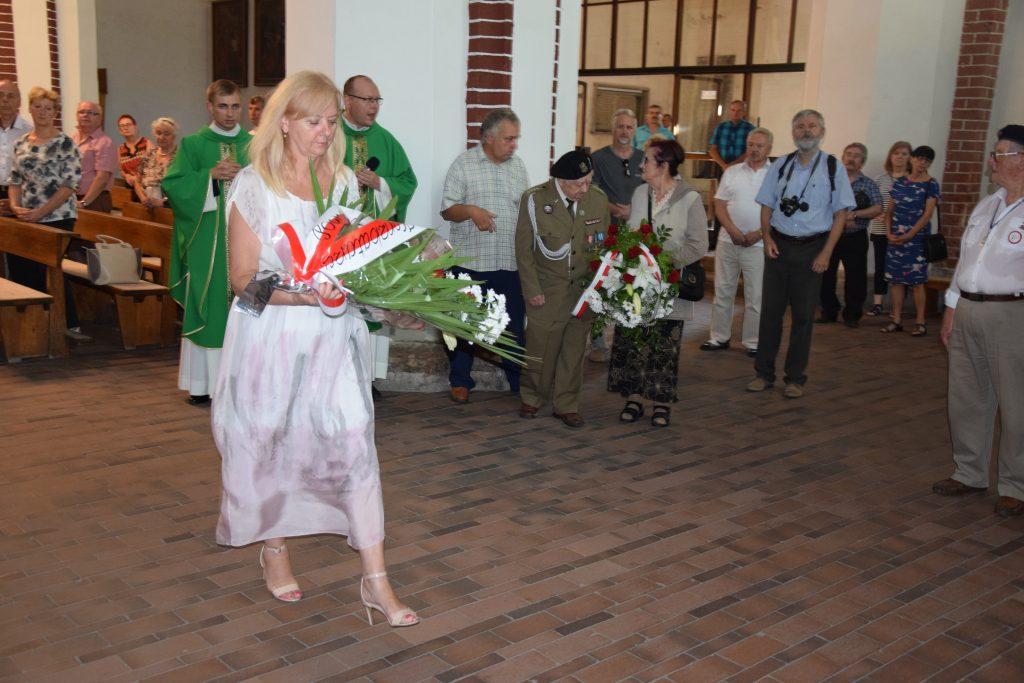 Sekretarz Powiatu Brzeskiego Genowefa Prorok składa wieniec pod pamiątkową tablicą w kościele pw. św. Mikołaja