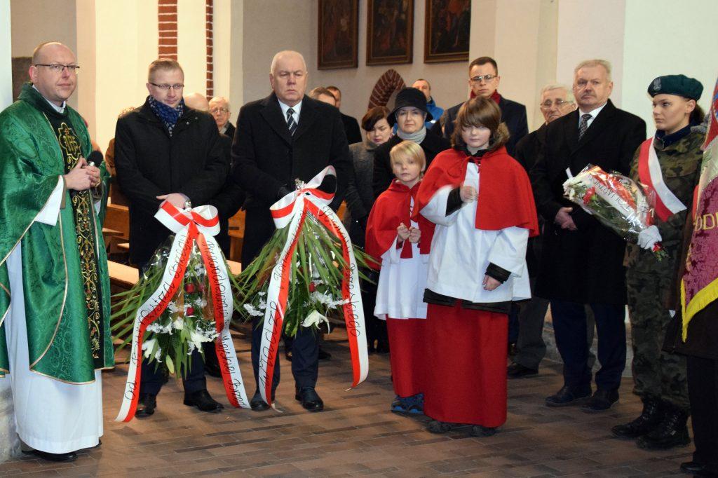 Starosta Maciej Stefański i Wiceburmistrz Tomasz Witkowski składają wiązanki kwiatów pod tablicą upamiętniającą Polaków zesłanych na Sybir